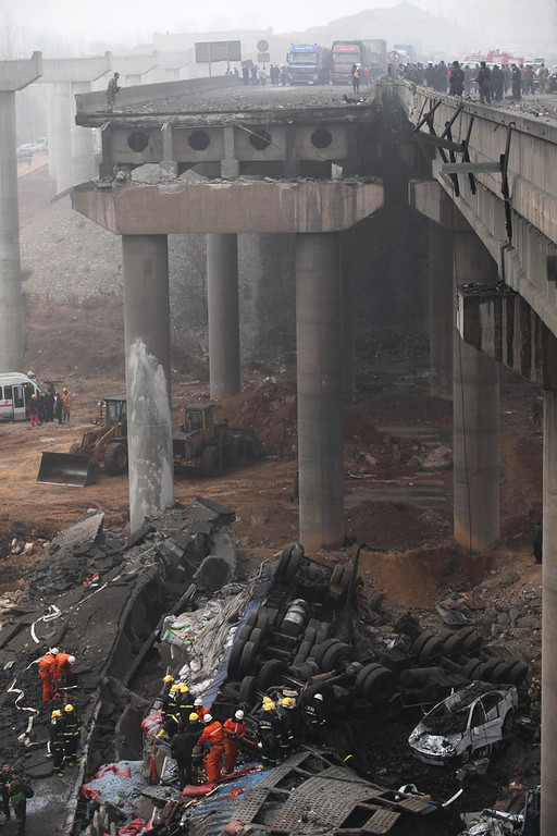 Description of . Rescuers (bottom) work at the scene of the collapsed Yichang bridge near the city of Sanmenxia, central China's Henan province, on February 1, 2013 after a fireworks-laden truck exploded as it crossed the bridge killing 26 people as the structure collapsed and vehicles plummeted to the ground, state-run media reported. An 80-meter long part of the bridge collapsed and six vehicles had been retrieved from the debris, China's official news agency Xinhua said. The bridge near the city of Sanmenxia is on the G30 expressway, the longest road in China, which stretches for nearly 4,400 kilometers (2,700 miles) from China's western border with Kazakhstan to the eastern Yellow Sea. AFP PHOTO STR/AFP/Getty Images