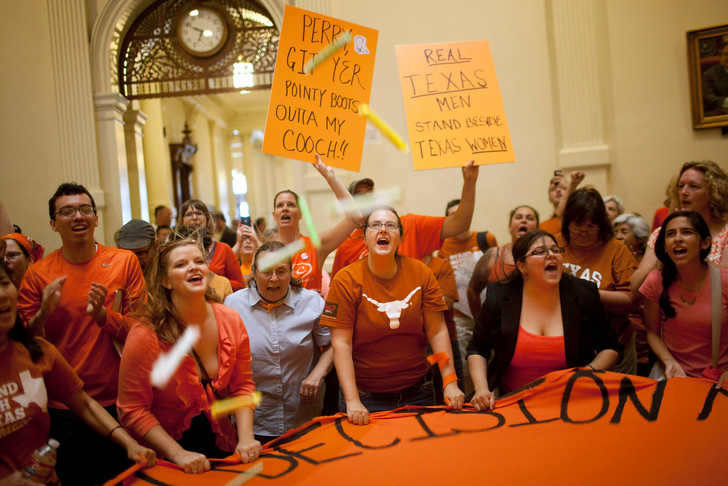 Description of . Abortion rights supporters rally on the floor of the State Capitol rotunda in Austin, Texas on Friday, July 12, 2013. The Texas Senate convened Friday afternoon to debate and ultimately vote on some of the nation's toughest abortion restrictions, its actions being watched by fervent demonstrators on either side of the issue. (AP Photo/Tamir Kalifa)