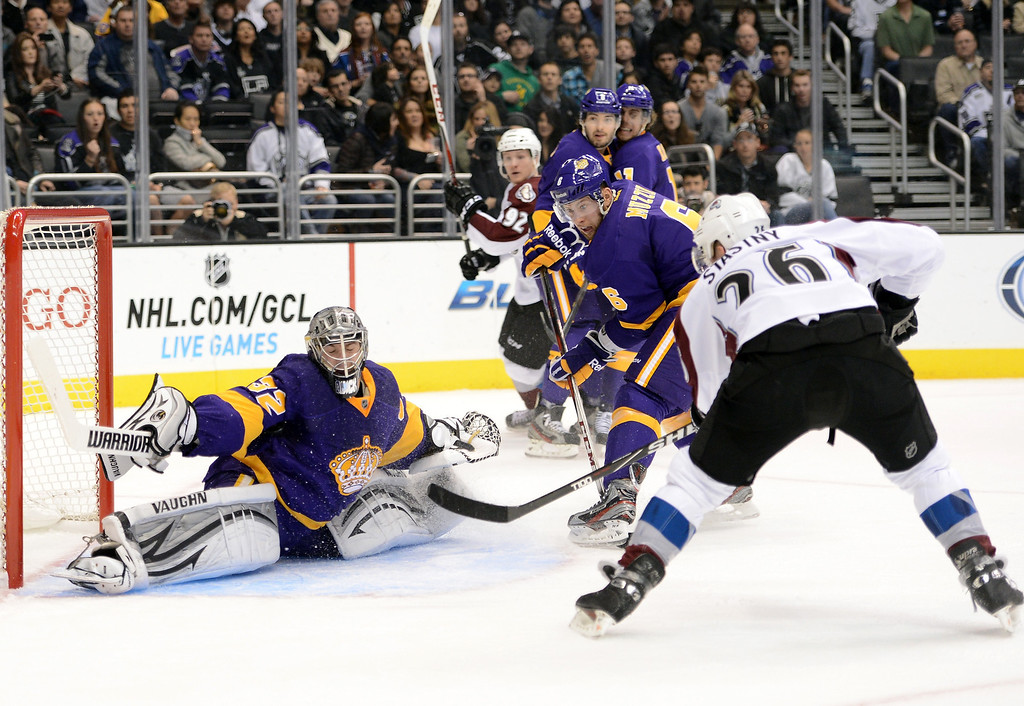 Description of . LOS ANGELES, CA - FEBRUARY 23:  Jonathan Quick #32 of the Los Angeles Kings makes a save off a shot from Paul Stastny #26 of the Colorado Avalanche as Jake Muzzin #6 of the Los Angeles Kings looks for a rebound during the game against the Colorado Avalanche at Staples Center on February 23, 2013 in Los Angeles, California.  (Photo by Harry How/Getty Images)