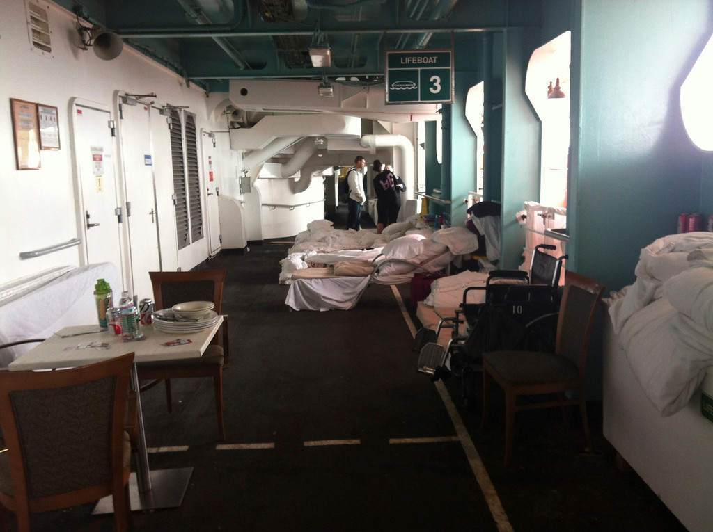 Description of . Beds line one of the outdoor decks on the Carnival Cruise ship Triumph in this February 14, 2013 handout photo courtesy of Jacob Combs. Passengers took to sleeping on outside decks after the Triumph lost power February 10 after a fire in the engine room, which left 4,220 people enduring food shortages and unsanitary conditions.  REUTERS/Jacob Combs/Handout