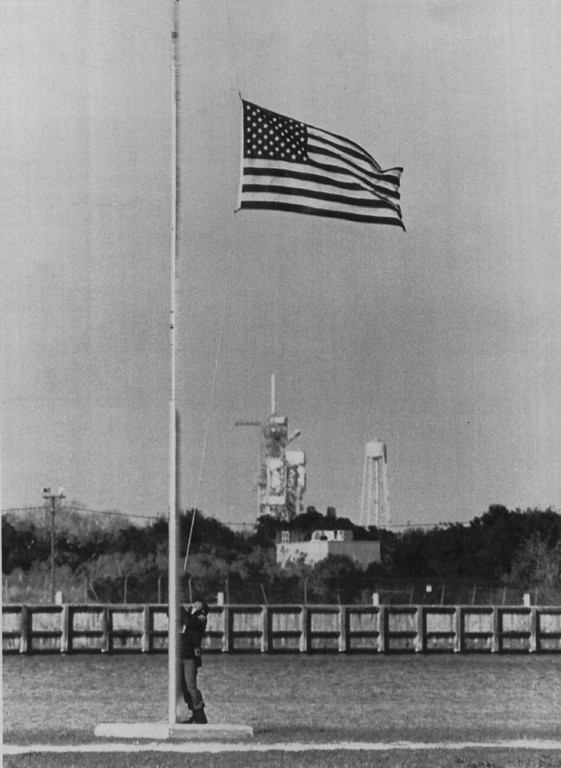 Description of . A Kennedy Space Center security guard lowers the flag to half mast at the press center on Jan. 28, 1986 in memory of the seven astronauts that perished aboard space shuttle Challenger. Launch pad 39B where the orbiter lifted off can be seen in the background.  Denver Post Library Archive