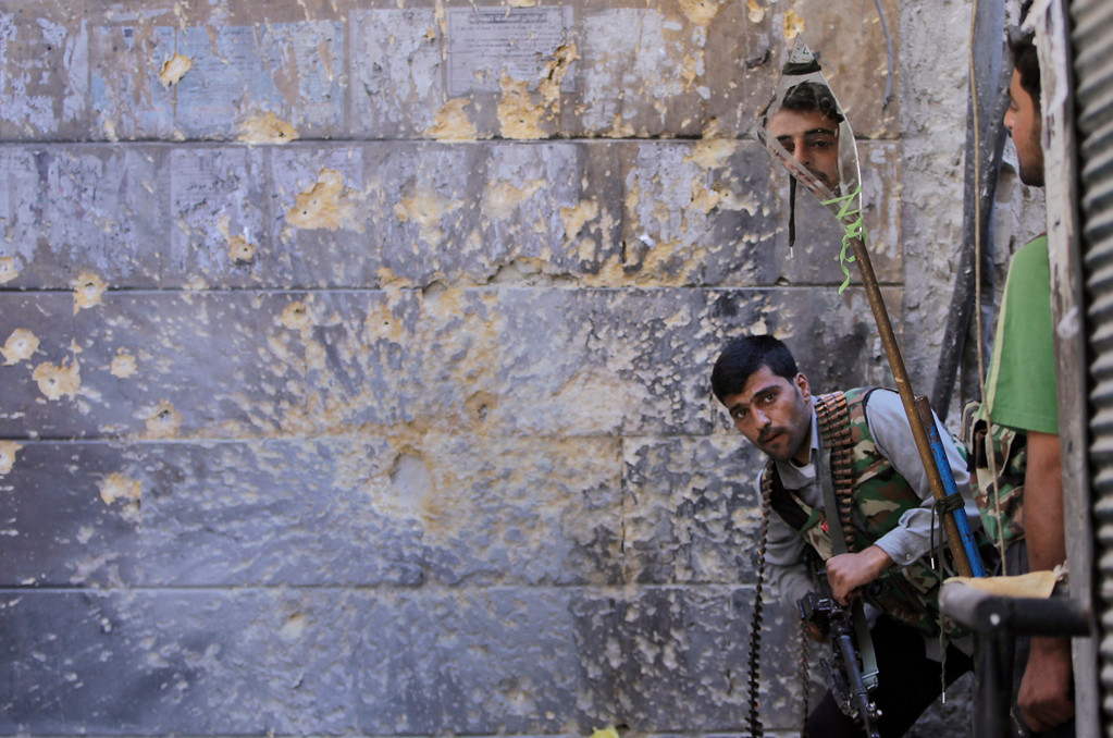 Description of . In this Sept. 24, 2012 file photo, a Free Syrian Army soldier, right, looks through a mirror which helps him see Syrian troops from the other side, as he takes his position with his comrade during fighting, at the old city of Aleppo city, Syria.  (AP Photo/Hussein Malla, File)