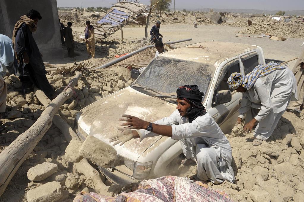 Description of . Pakistani survivors clear the debris of destroyed houses in the earthquake-devastated district of Awaran on September 25, 2013.   AFP PHOTO/Banaras  KHAN/AFP/Getty Images