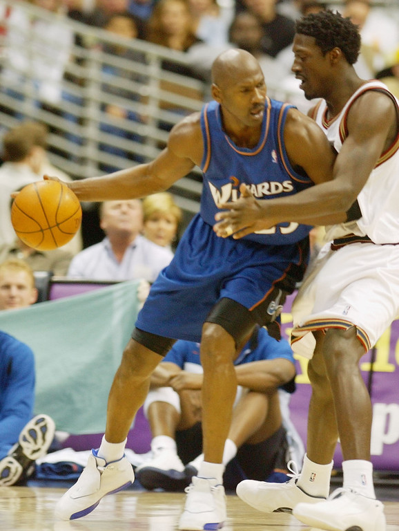 Description of . Washington Wizards guard Michael Jordan, left, works the ball inside for a shot against Denver Nuggets forward Donnell Harvey in the first quarter in Denver on Sunday, March 30, 2003. (AP Photo/David Zalubowski)