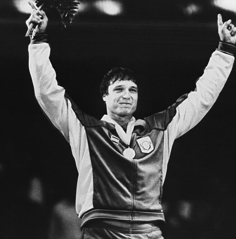 Description of . FILE - This Aug. 3, 1984 file photo shows Greco-Roman wrestling gold medalist Jeff Blatnick gesturing during ceremonies at the Summer Olympics in Los Angeles.  Blatnick, who overcame cancer to win a gold medal in Greco-Roman wrestling at the 1984 Summer Olympics, has died in New York state at age 55.  Ellis Hospital in Schenectady, N.Y., said Wednesday Oct. 24, 2012, that he died there of heart failure.(AP Photo/Doug Pizac, File)
