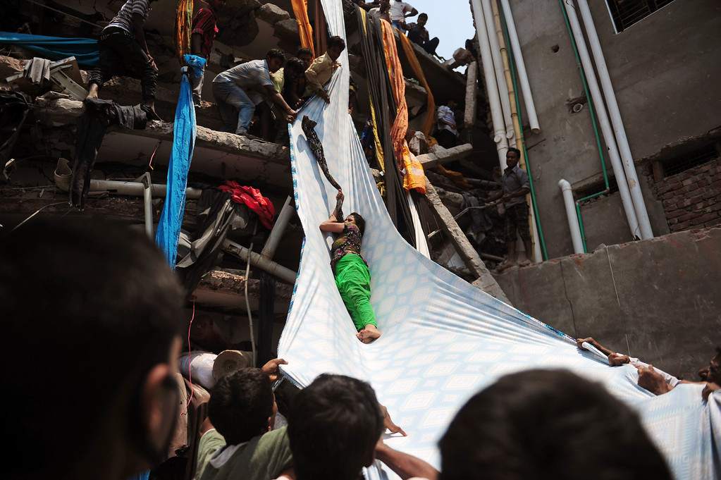 Description of . Bangladeshi garment workers help evacuate a survivor using lengths of textile as a slide to evacuate from the rubble after an eight-story building collapsed in Savar, on the outskirts of Dhaka, on April 24, 2013.  AFP PHOTO/Munir uz  ZAMAN/AFP/Getty Images