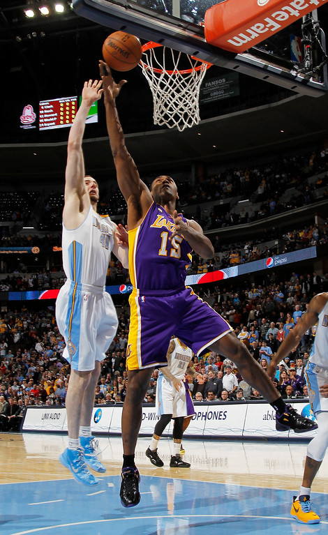 Description of . Los Angeles Lakers forward Metta World Peace, right, goes up for a shot as Denver Nuggets center Kosta Koufos defends in the first quarter of an NBA basketball game in Denver on Monday, Feb. 25, 2013. (AP Photo/David Zalubowski)