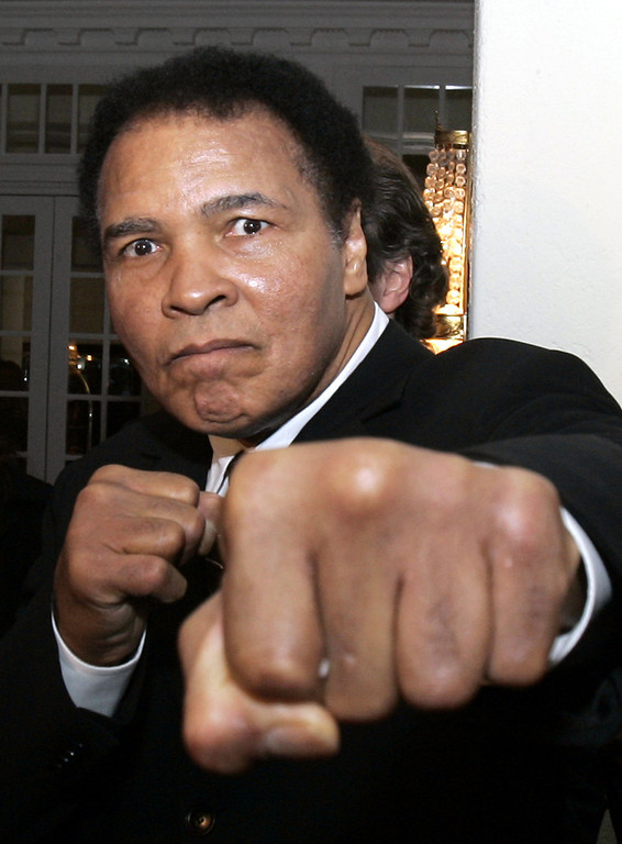 Description of . Former heavyweight boxing champion Muhammad Ali gestures toward photographers in a hotel lobby in Davos, Switzerland, in this Jan. 28, 2006 file photo.  (AP Photo/Michel Euler)