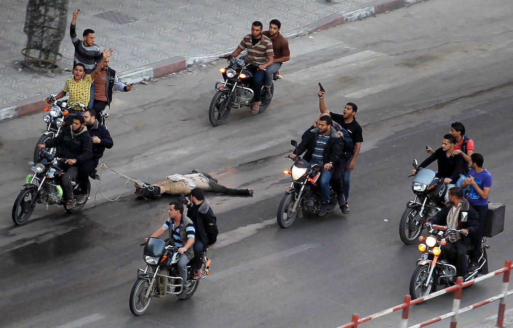 Description of . Palestinian gunmen ride motorcycles as they drag  the body of a man, who was suspected of working for Israel, in Gaza City November 20, 2012. Palestinian gunmen shot dead six alleged collaborators in the Gaza Strip who