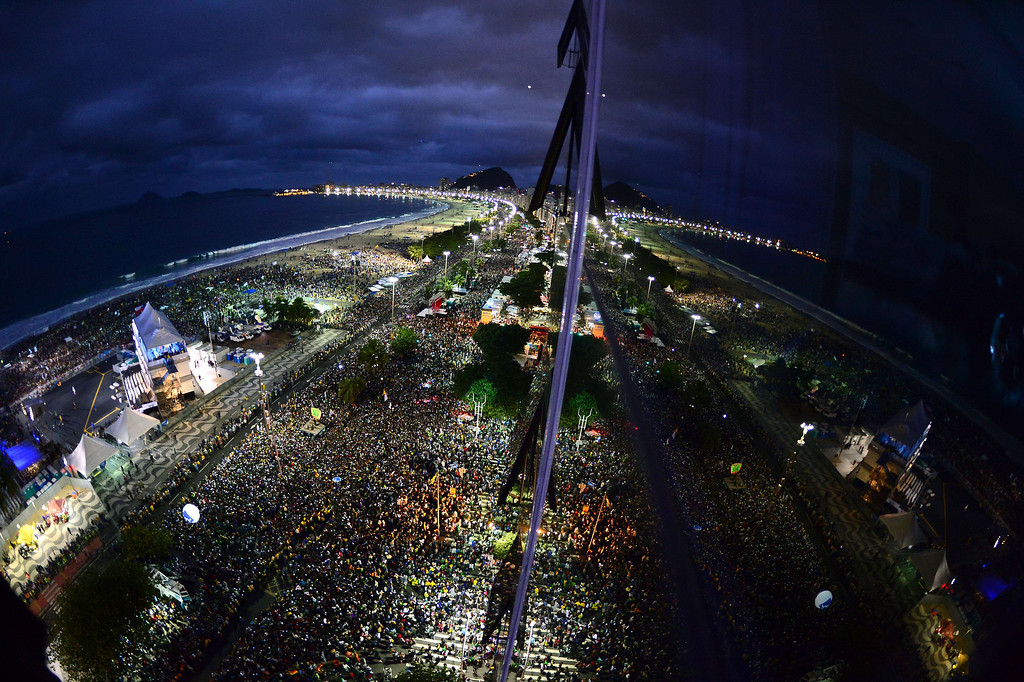 Description of . Thousands of young people gather at Rio de Janeiro's iconic Copacabana beachfront on July 25, 2013 for the welcoming of Pope Francis to World Youth Day ceremonies. On the fourth day of his visit to Brazil and borne along by adoring crowds, Pope Francis waded into the country's ramshackle slums and onto the front line of its fierce national battle over poverty and corruption, before going to the much wealthier district of Copacabana for his welcome by the youth.   CHRISTOPHE SIMON/AFP/Getty Images