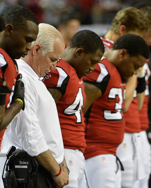 Description of . Atlanta Falcons head coach Mike Smith, second from left, and players close their eyes during during a moment of silence for the victims of the Sandy Hook Elementary School shootings before an NFL football game against the New York Giants, Sunday, Dec. 16, 2012, in Atlanta. A gunman walked into the school in Newtown, Conn., Friday and opened fire, killing 26 people, including 20 children. (AP Photo/Rich Addicks)