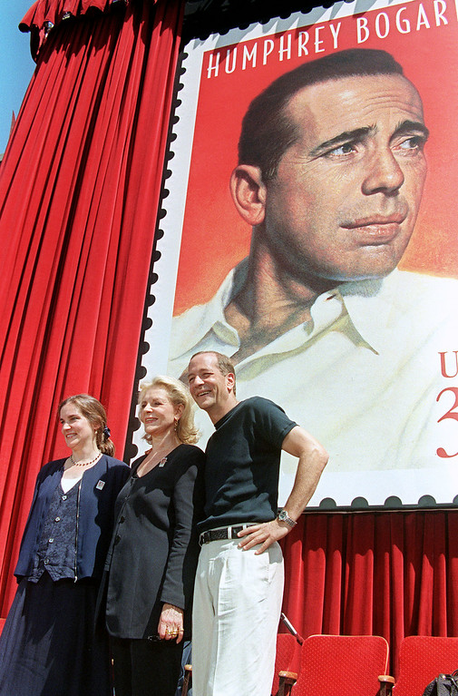 ". FILE - AUGUST 12: It has been reported that actress Lauren Bacall has died of a stroke. She was 89 years old. Actress Lauren Bacall (C) and her two children Stephen (R) and Leslie (L) by former husband Humphrey Bogart pose in front of a stamp commemorating his life 31 July during a stamp unveiling ceremony in Hollywood. The stamp portrait is from the movie poster for the 1946 film ""The Big Sleep\"". Bogart died 40 years ago and is celebrated in the Hollywood Legends stamp series.   (Photo credit should read MIKE NELSON/AFP/Getty Images)"
