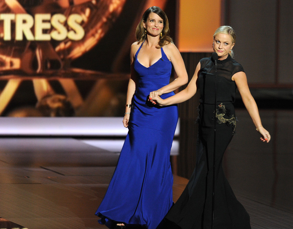 Description of . Writer/actresses Tina Fey and Amy Poehler speak onstage during the 65th Annual Primetime Emmy Awards held at Nokia Theatre L.A. Live on September 22, 2013 in Los Angeles, California.  (Photo by Kevin Winter/Getty Images)