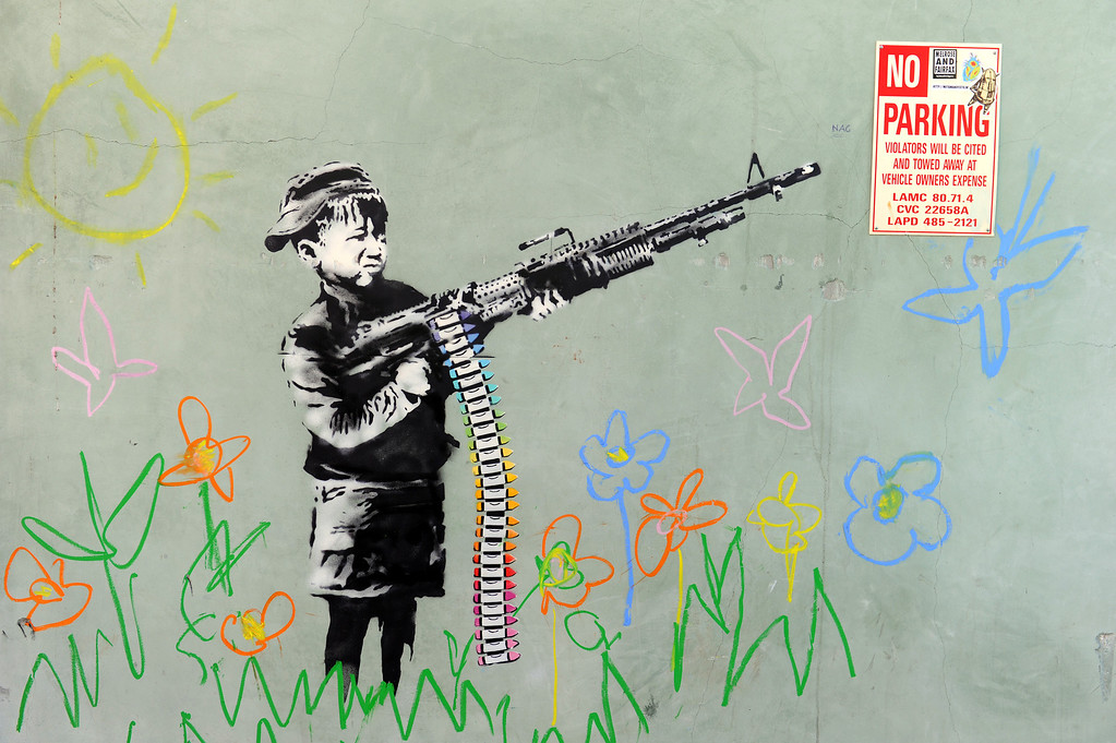 Description of . A graffiti attributed to secretive British artist Banksy depicting a child wielding a machine gun, in black and white surrounded by colored flowers, is spotted in Westwood, California on February 17, 2011. Another graffiti was ripped down Wednesday, February 16th in Hollywood, amid sightings of other pieces in a reported pre-Oscars publicity stunt. Banksy is nominated for best documentary for
