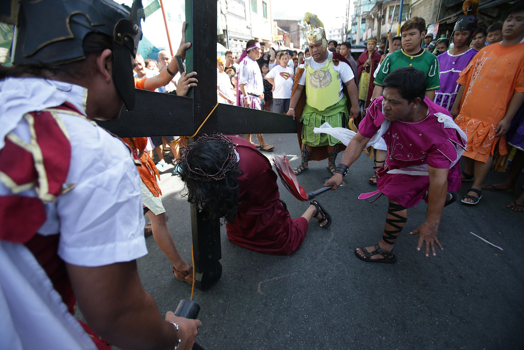 Description of . A man portraying Jesus Christ is whipped by a fellow actor during a reenactment of Christ' suffering and death as part of Maundy Thursday rituals to atone for sins, in suburban Mandaluyong, east of Manila, Philippines, on Thursday, March 28, 2013. The ritual is frowned upon by church leaders in this predominantly Roman Catholic country. (AP Photo/Aaron Favila)