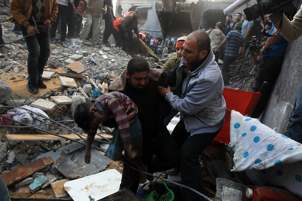 . A Palestinian man carries the body of a child from the al-Dallu family out from the rubble after an Israeli missile struck a family home killing at least seven members of the same family in Gaza City on November 18, 2012. (MAHMUD HAMS/AFP/Getty Images)