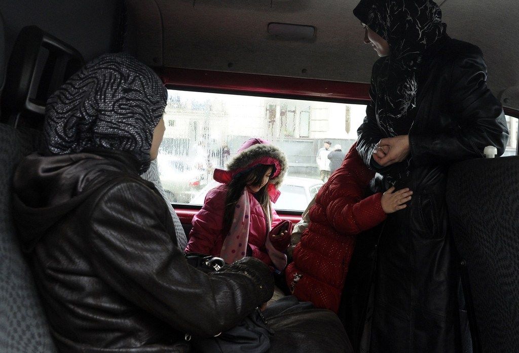 Description of . Crimean Tartar women with their children leave the train station in Lviv by car after disembarking from a train from Simferopol, on March 7, 2014, in the western Ukrainian city of Lviv. In the city of Lviv, across Ukraine from the crisis gripping Crimea, a group of Tatars fleeing the troubled peninsula disembarks on a train platform looking for security away from Russian forces. YURIY DYACHYSHYN/AFP/Getty Images