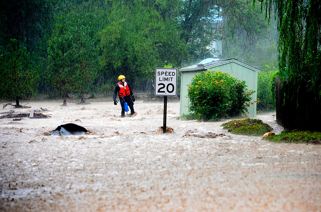 Description of . BOULDER, CO - SEPTEMBER 12: A Rescue worker goes door to door checking on residents in north Boulder, September 12, 2013. Massive flash flooding is ongoing along the Front Range of Colorado. (Photo By RJ Sangosti/The Denver Post)