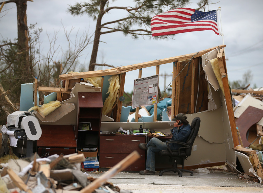 Description of . A man who wished not to be identified talks on a phone in a business that was destroyed by a tornado, April 30, 2014 in Mayflower, Arkansas. Deadly tornadoes ripped through the region starting on April 27 leaving more than two dozen dead. The storm system has also brought severe flooding to Florida's Panhandle.  (Photo by Mark Wilson/Getty Images)