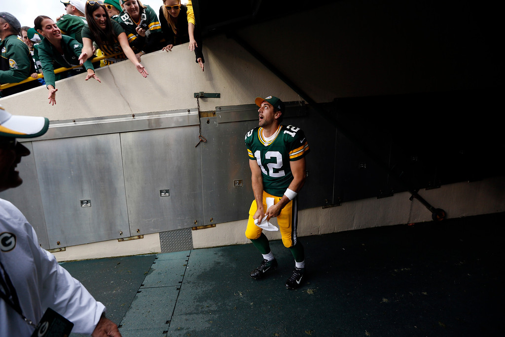Description of . Green Bay Packers' Aaron Rodgers throws his towel to some fans after an NFL football game against the Washington Redskins Sunday, Sept. 15, 2013, in Green Bay, Wis. The Packers won 38-20. (AP Photo/Mike Roemer)