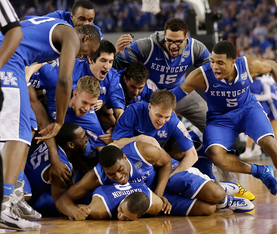 Description of . Kentucky players celebrate on the court after their 74-73 victory over Wisconsin in an NCAA Final Four tournament college basketball semifinal game Saturday, April 5, 2014, in Arlington, Texas. (AP Photo/Eric Gay)