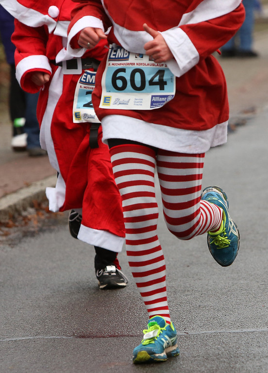 Description of . A participant competes in the 5th annual Michendorf Santa Run (Michendorfer Nikolauslauf) on December 8, 2013 in Michendorf, Germany. Over 900 people took part in this year's races, which included one for children and one for adults.  (Photo by Adam Berry/Getty Images)
