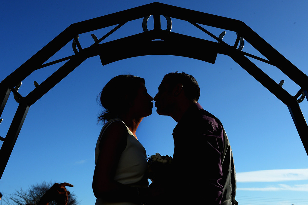 Description of . Michael Lewis and Rebecca Anderson kiss outside the Gretna Green Famous Blacksmiths Shop on the day of their wedding on Valentine's day on February 14, 2013 in Gretna,Scotland. Gretna Green is one of the most popular wedding destinations in Scotland hosting thousands of weddings each year with a particular rise on St Valentine's Day. Gretna Green has been hosting marriages in the blacksmiths shop since 1754.  (Photo by Jeff J Mitchell/Getty Images)