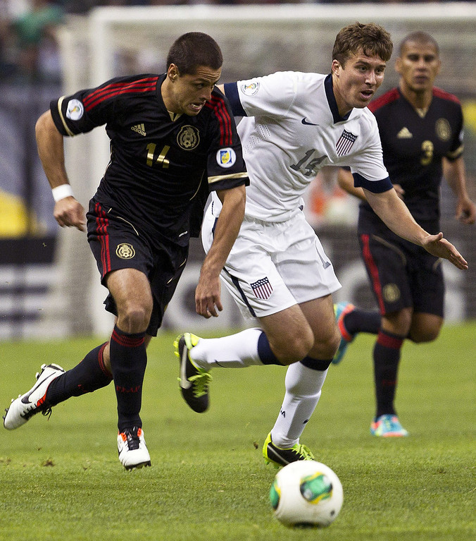 Description of . Mexico's Javier Hernandez, left, and United States' Matt Besler vie for the ball during a 2014 World Cup qualifying match at the Aztec stadium in Mexico City, Tuesday, March 26, 2013. (AP Photo/Christian Palma)