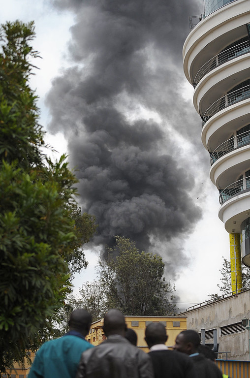 Description of . People watch a column of smoke rise on September 23, 2013 in the vicinity of the besieged Westgate shopping mall in Nairobi following a loud explosion.                  AFP PHOTO / TONY  KARUMBA/AFP/Getty Images