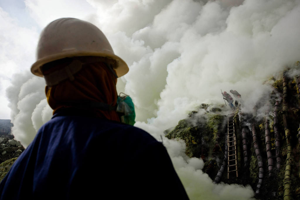 Description of . A sulfur miner looks at the crater as they prepare to bury the head in the crater as part of an annual offering ceremony on the Ijen volcano on December 17, 2013 in Yogyakarta, Indonesia.  (Photo by Ulet Ifansasti/Getty Images)