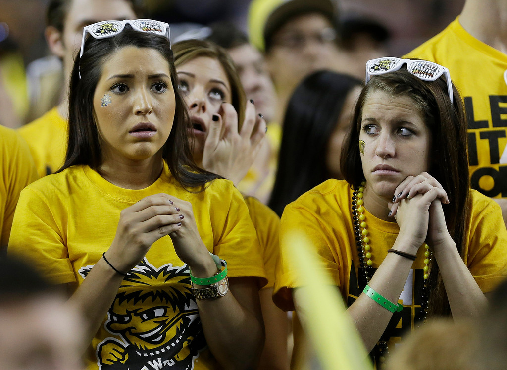 Description of . Wichita State fans watch play against Louisville during the second half of the NCAA Final Four tournament college basketball semifinal game Saturday, April 6, 2013, in Atlanta. (AP Photo/Charlie Neibergall)