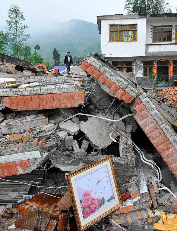 Description of . This photo taken on April 23, 2013 shows a man walking over rubble of collapsed houses in Lushan county of Yaan, southwest China's Sichuan province. Tens of thousands of homeless survivors of China's devastating quake are living in makeshift tents or on the streets, facing shortages of food and supplies as well as an uncertain future.   AFP/Getty Images