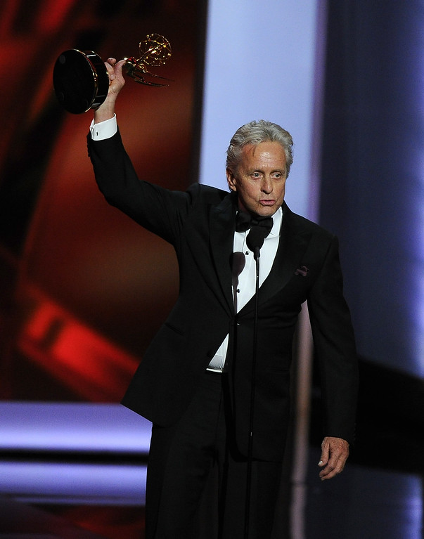 Description of . Michael Douglas accepts the award for for outstanding lead actor in a miniseries or movie for his role in ìBehind The Candelabraî at the 65th Primetime Emmy Awards at Nokia Theatre on Sunday Sept. 22, 2013, in Los Angeles.  (Photo by Chris Pizzello/Invision/AP)