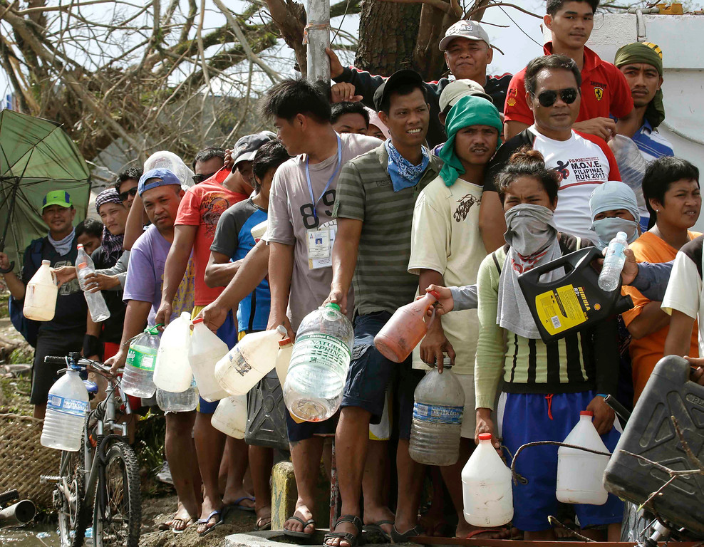 Description of . Typhoon survivors line up to get fuel from an abandoned filling station Thursday, Nov. 14, 2013, in Tacloban city, Leyte province in central Philippines. Aid has been slow to reach the half-million people displaced by the storm that tore across several islands in eastern Philippines last Friday. (AP Photo/Bullit Marquez)