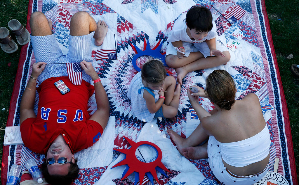 Description of . The Walker family of Lafayette, La. relaxes while waiting for the start of the Boston Pops Fourth of July Concert at the Hatch Shell in Boston, Thursday, July 4, 2013. (AP Photo/Michael Dwyer)