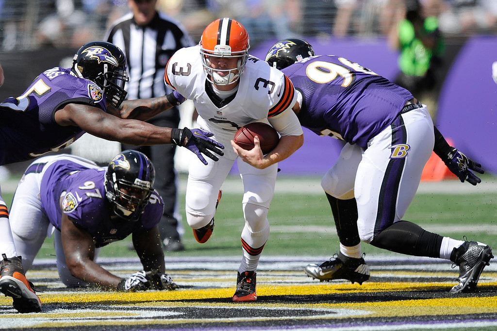 Description of . Cleveland Browns quarterback Brandon Weeden (3) scrambles between Baltimore Ravens outside linebacker Terrell Suggs, top left, defensive end Arthur Jones (97) and defensive end Marcus Spears, right, during the first half of an NFL football game in Baltimore, Md., Sunday, Sept. 15, 2013. (AP Photo/Nick Wass)