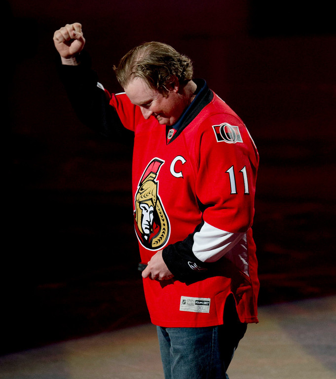 . PGA golfer Brad Fritsch raises his arm as he is acknowledged by the home-town crowd before the ceremonial puck drop at an NHL hockey game between the Ottawa Senators and New York Rangers in Ottawa, Ontario, Thursday, Feb. 21, 2013. (AP Photo/The Canadian Press, Adrian Wyld)