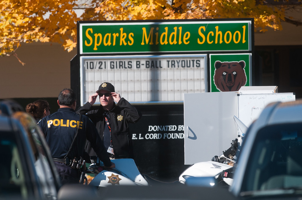 Description of . Law enforcement gather in the parking lot after a shooting at Sparks Middle School October 21, 2013 in Sparks, Nevada. A staff member was killed and two students were injured after a student opened fire at the Nevada middle school. The suspected gunman was also killed. (Photo by David Calvert/Getty Images)