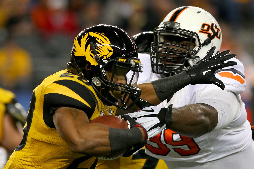 Description of . ARLINGTON, TX - JANUARY 03:  Running back Henry Josey #20 of the Missouri Tigers runs against Calvin Barnett #99 of the Oklahoma State Cowboys in the first half during the AT&T Cotton Bowl on January 3, 2014 in Arlington, Texas.  (Photo by Ronald Martinez/Getty Images)