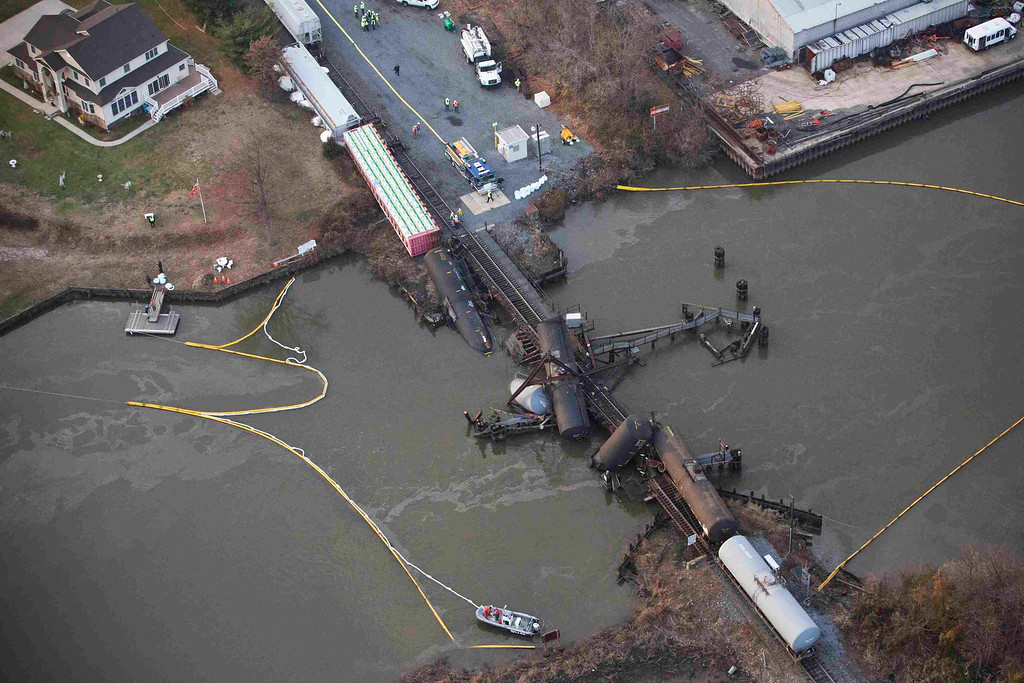 Description of . Derailed freight train cars sit semi-submerged in the waters  of Mantua Creek after a train crash in Paulsboro, New Jersey November 30, 2012. A rail bridge collapsed on Friday over a creek in southern New Jersey, causing a Conrail freight train to derail and spill hazardous chemicals into the air and water, authorities said.  REUTERS/Andrew Burton