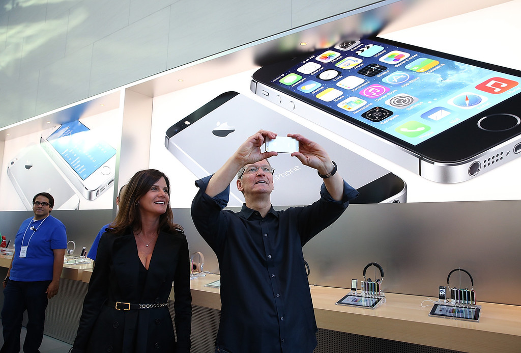 Description of . Katie Cotton, Apple vice president of corporate communications (L) looks on as Apple CEO Tim Cook (R) uses an iPhone to take a picture of customers waiting in front of an Apple store to purchase the new iPhones on September 20, 2013 in Palo Alto, California. Apple launched two new models of iPhone: the iPhone 5S, which is preceded by the iPhone 5, and a cheaper, paired down version, the iPhone 5C. The phones come with a new operating system.  (Photo by Justin Sullivan/Getty Images)