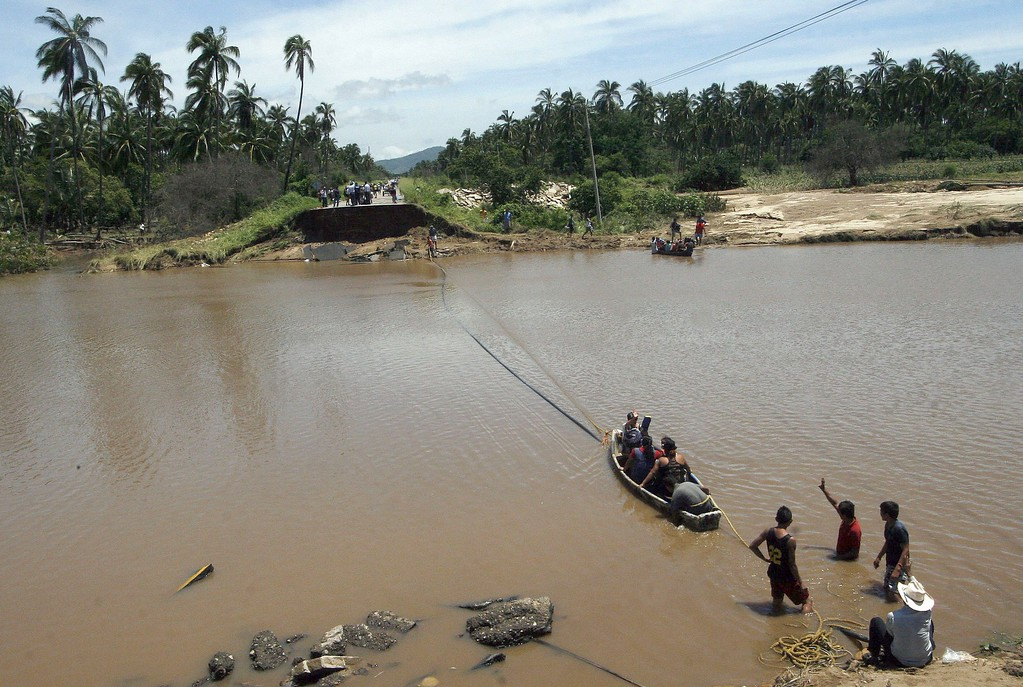 Description of . People cross the river near a destroyed bridge in Coyuca de Benitez, Guerrero state, Mexico, after heavy rains hit the area on September 18, 2013.  AFP PHOTO/ Pedro  PARDO/AFP/Getty Images