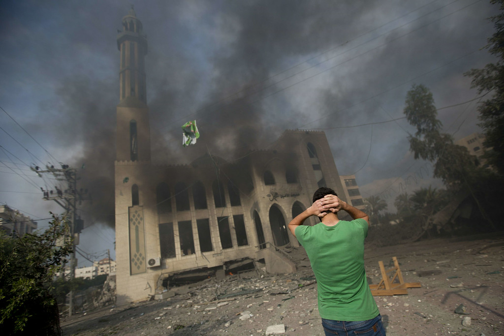 Description of . A Palestinian man reacts in front of a destroyed mosque after it was hit by an Israeli air strike, on July 29, 2014, in Gaza City. Bloodshed in and around Gaza surged with strikes killing at least 13 Palestinians, a day after five Israeli soldiers died, shattering hopes for an end to three weeks of violence. AFP PHOTO/MAHMUD  HAMS/AFP/Getty Images