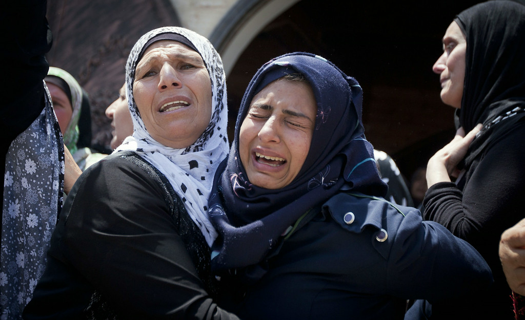 Description of . A relative of Palestinian Mahmoud Shawamreh cries during his funeral in the West Bank village of Al-Ram, Tuesday, July 22, 2014. Shawamreh, 21, died after he was shot during clashes with Israeli troops Monday. (AP Photo/Majdi Mohammed)