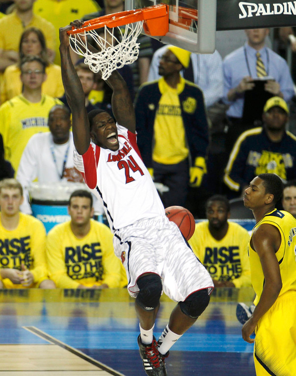 Description of . Louisville Cardinals forward Montrezl Harrell (24) dunks next to Michigan Wolverines forward Glenn Robinson III (R) in the first half of their NCAA men's Final Four championship basketball game in Atlanta, Georgia April 8, 2013. REUTERS/Tami Chappell