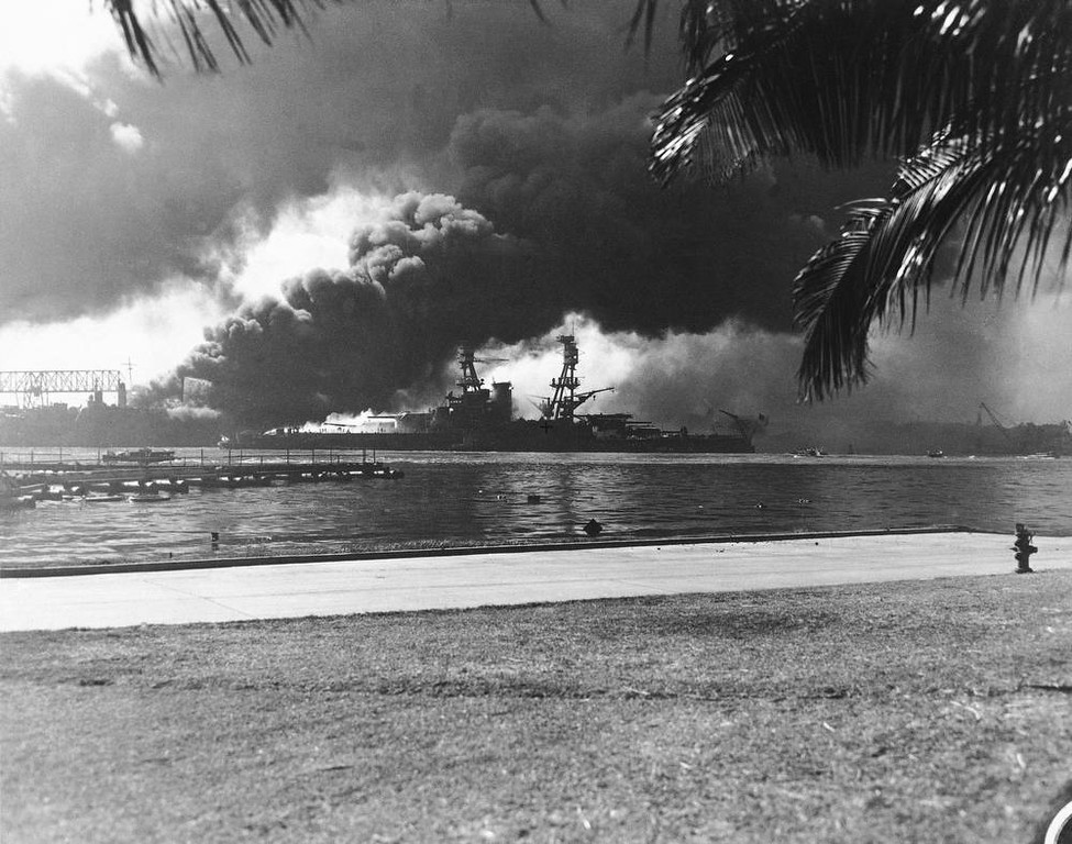 Description of . In this image provided by the U.S. Navy, the battleship USS Nevada, right, and the destroyer USS Shaw, left, burn following the attack at Pearl Harbor, Hawaii on Dec. 7, 1941. The Nevada was run aground to keep from sinking in the main channel. (AP Photo/U.S. Navy)