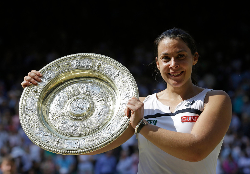 Description of . Marion Bartoli of France smiles as she holds the trophy after winning the Women's singles final match against Sabine Lisicki of Germany at the All England Lawn Tennis Championships in Wimbledon, London, Saturday, July 6, 2013. (AP Photo/Anja Niedringhaus)