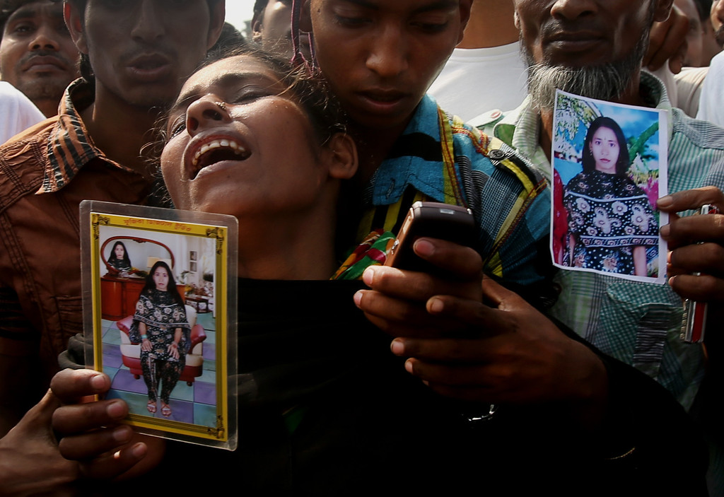 Description of . A woman mourns as she arrived in hopes to find her sister, seen in the photograph she is holding, among unclaimed bodies brought to a cemetery from the garment factory building collapse in preparation for a mass burial on Wednesday May 1, 2013 in Dhaka, Bangladesh. (AP Photo/Wong Maye-E)