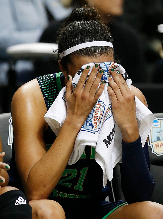 Description of . Notre Dame guard Kayla McBride (21) sits on the bench after the second half of the championship game against Connecticut in the Final Four of the NCAA women's college basketball tournament, Tuesday, April 8, 2014, in Nashville, Tenn. Connecticut won 79-58.(AP Photo/Mark Humphrey)