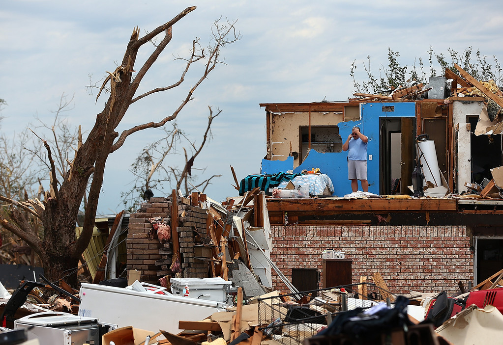 Description of . MOORE, OK - MAY 23:  Steve Gerberth takes a phone call from the second story of his destroyed home on May 23, 2013 in Moore, Oklahoma. The tornado of at least EF4 strength and two miles wide touched down May 20 killing at least 24 people and leaving behind extensive damage to homes and businesses. U.S. President Barack Obama promised federal aid to supplement state and local recovery efforts.  (Photo by Tom Pennington/Getty Images)